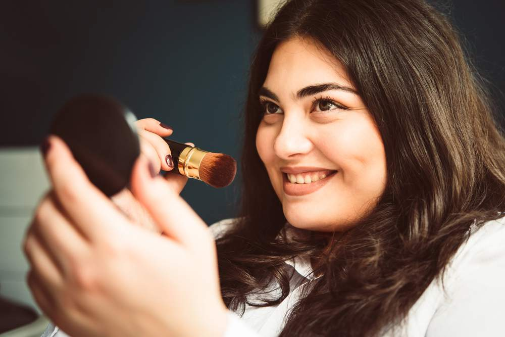 plus size model putting on makeup