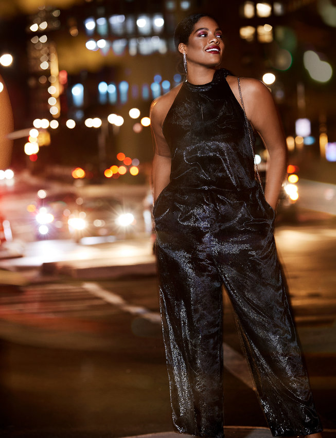 A plus size woman walking the street in an Eloquii Plus size Lurex Vevet Jumpsuit