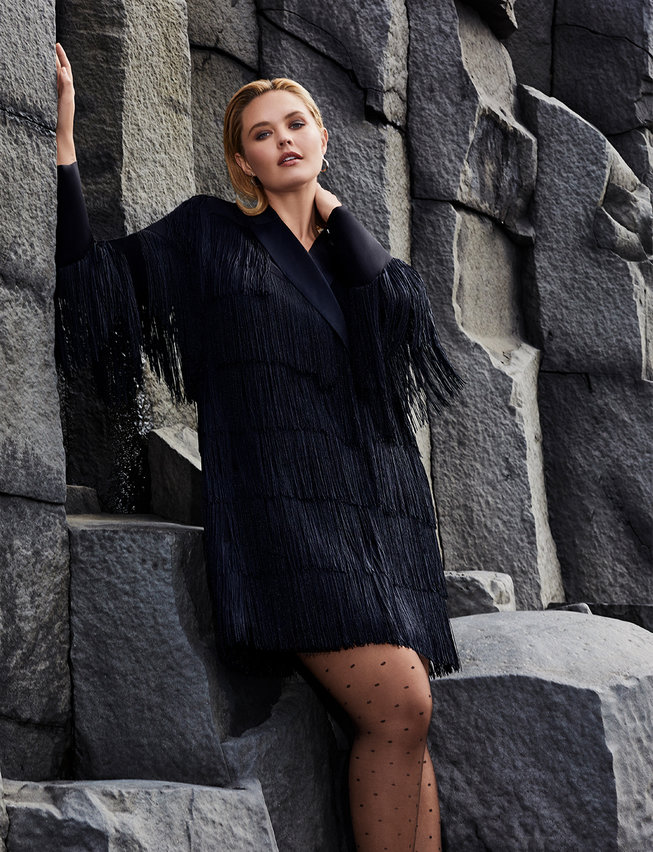 A woman standing in a Plus Size Fringe Blazer Dress from Eloquii